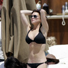 Lindsay Lohan exposed her boobs being felt in a black bikini